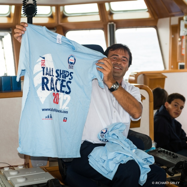 Getting in the mood, the Captain of the Coastguard vessel, Sebastián de Ocampo, tries on a Tall Ship t-shirt